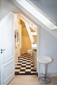 Vintage bar stool next to open door with view into rustic, attic bathroom with black and white chequered floor