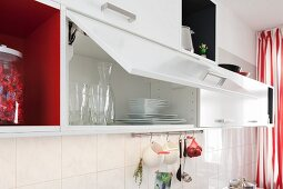 White wall cupboards with an open door in a renovated kitchen