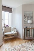 Elegant, neoclassical-style bench in niche and chest of drawers with modern, striped pattern in bedroom