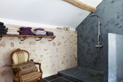 Antique armchair next to slate-grey, modern shower area in renovated country house with stone wall