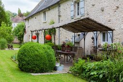 Terrace with metal pergola decorated with lanterns in well-tended garden adjoining stone country house