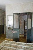 Flügeltür zum Bad Ensuite, in Grautönen marmorierte Wände und gelbliche Terrakottafliesen, vorne Doppelbett mit gestreifter Steppdecke