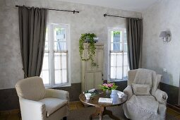 Two armchairs with loose covers flanking round Biedermeier table in front of windows with long curtains and potted ivy on old cabinet