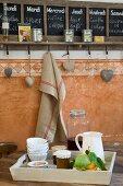 Wandtafel mit Tageseinteilung, Herzendeko und Leinentuch an Haken, Frühstückstablett mit frischen Zitronen im Vordergrund