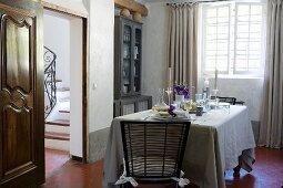 Gedeckter Tisch in provenzalischem Esszimmer mit weißem Kalkanstrich