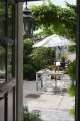 View into idyllic courtyard with greenery, vintage-style garden furniture and white parasol