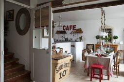 Festlich gedeckter Esstisch in offener Landhausküche und Blick auf Vintage-Treppenaufgang