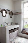 Masonry washstand with twin sinks below round mirrors in renovated bathroom with cement floor tiles