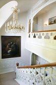 Kristallleuchter und Ölgemälde im noblen Treppenaufgang, verzierte Geländer
