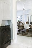 View from hallway with iron, wood-burning stove into country-house kitchen-dining room with Windsor chairs