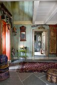 Foyer of wooden house with painted walls, open interior doors and rug on stone floor