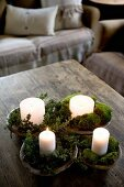 Moos und kleine Zweige um brennende Kerzen dekoriert, in Holzschalen