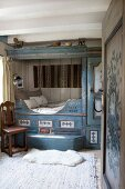 Steps leading to double cubby bed painted blue with floral motifs and white animal-skin rug on carpet