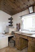 Rustikaler Waschtisch aus Holz vor Fenster, seitlich Kissen auf Ablage vor Badewanne