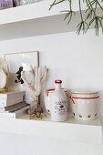 Ceramic oil bottle and retro storage jars on white shelf