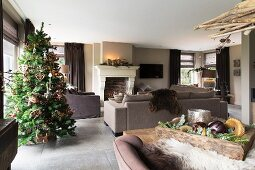 Decorated Christmas tree in open-plan interior with fireplace