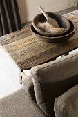 Wooden bowls, wooden paddle and piece of fur on rustic table