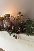Festive arrangement of cherub ornament on rod and lit candles in wooden candlesticks on shelf
