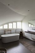 Free-standing bathtub in designer bathroom with vaulted ceiling and curved windows