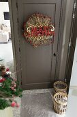 Christmas decorations and greetings hung on front door painted dark grey