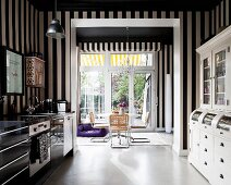 Kitchen with black and white striped wallpaper, modern kitchen counter and retro dresser painted white; dining area with cantilever chairs in background
