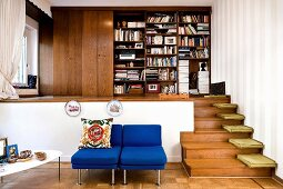 Blue easy chairs in front of raised platform, floor cushions on wooden steps and simple fitted bookcase