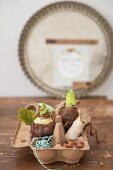 Egg box decorated with rustic items; nuts, mushrooms and flower bulbs