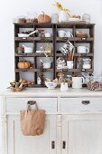 White-painted dresser with crockery and autumnal decorations in old display cases on top