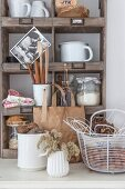 Kitchen utensils and autumnal decorations on surface and in repurposed display case
