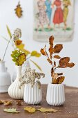Branches of autumnal leaves in white, ceramic vases on table