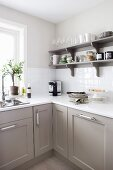 Corner of kitchen with white worksurface on grey-painted base units below colour-coordinated wall-mounted shelves