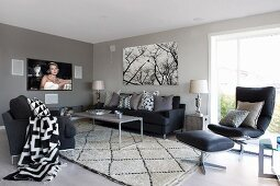 Grey-painted lounge area with black sofa and chairs around delicate coffee table on rug