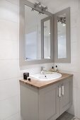 Washstand with grey-painted base unit, framed mirror and wall-mounted lamps in corner of bathroom
