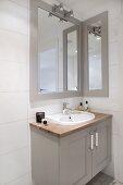 Waschtisch mit grau lackiertem Unterschrank und gerahmter Spiegel oberhalb Wandleuchte in Badezimmerecke