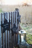 Star-shaped signs made from black-painted wood hanging on a fence with a lantern with a candle on a stone