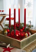 An advent's wreath in a wooden box with red baubles and four red, burning candles