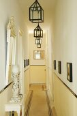 Long, narrow corridor in period apartment with row of lanterns hanging from ceiling