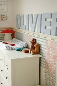 Soft toys on white chest of drawers in corner of nursery with ornamental letters on wall