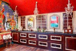 Orientalisch gestaltete Küche - Holzunterschränke mit vergoldeten Profilen in langer Küchenzeile, unter filigranen Kronleuchtern an roter Decke