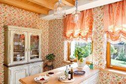 Frühstückstheke in Küche mit Landhaus Charme, an Wand geblümte Tapete und apricotfarbene Raffrollos am Fenster