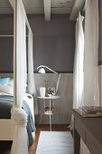 Four-poster bed with draped, transparent curtains next to lamp on delicate bedside table