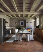 Chairs with loose white covers on terracotta floor in eclectic kitchen with white, wood-beamed ceiling