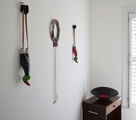 Slingshots with handles made from painted, stylised birds hanging from wall hooks and bowl on side table