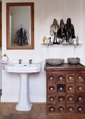 Antique apothecary cabinet next to pedestal sink in rustic bathroom