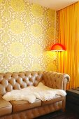 White, sheepskin blanket on brown, leather, button-tufted sofa; standard lamp with orange lampshade in corner against 70s-style, patterned wallpaper