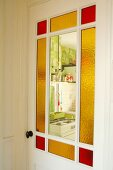 Vintage interior door with stained glass panels and view into kitchen