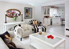Klassisches Wohnzimmer, naturfarbene und schwarz-weiss gestreifte Sitzmöbel um Couchtisch mit Glasfüllung, im Hintergrund breiter Durchgang und Blick in die Küche