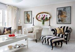 Heller, klassischer Wohnzimmer, Couchtisch mit Glasfüllung vor naturfarbenem Sessel und schwarzweiss gestreifter Fussschemel mit passendem Sessel