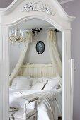 Spiegel mit weissem, geschnitztem Holzrahmen, darin reflektiertes Doppelbett mit weisser Bettwäsche und Baldachin