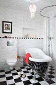 Freistehende Vintage Badewanne auf Schachbrettmusterboden vor halbhoher, weisser Fliesenwand, seitlich bodenebene Dusche